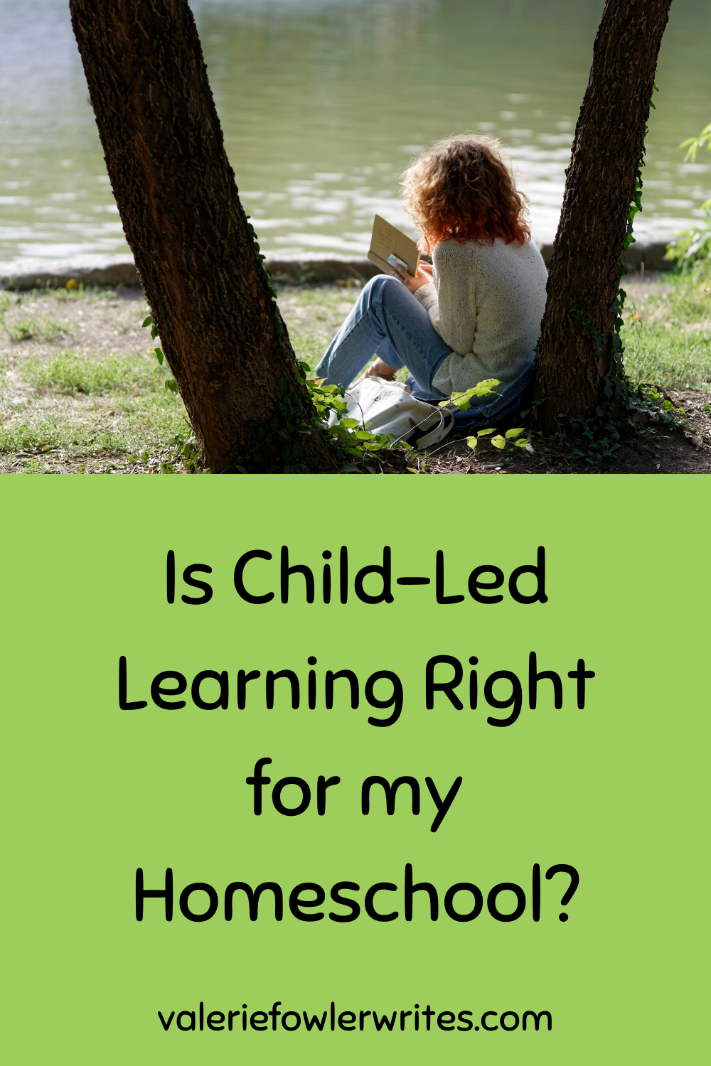 Child leaning against a tree by the lake reading a book.